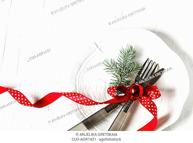 Fork and knife tied with a red ribbon and Christmas decor on white background with copy space. Food, restaurant and table setting theme, copy space