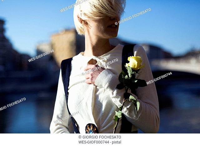 Italy, Verona, blond woman with yellow rose