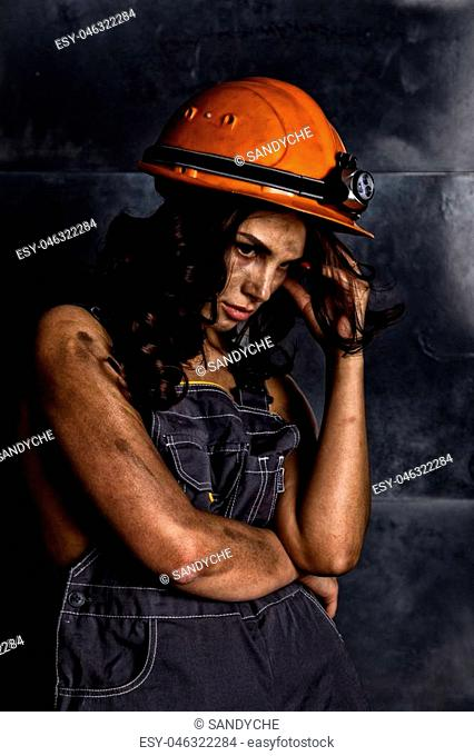 close-up portrait sexy female miner worker in coveralls over his naked body, helmet on the head with a flashlight