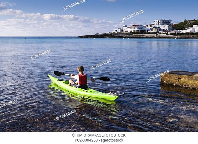 A teenage boy in a Kayak at Punta Prima , Menorca , Balearic Islands , Spain