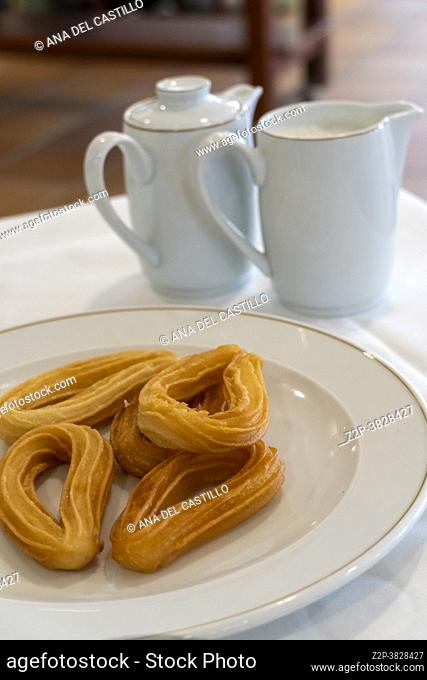 Spanish breakfast with churros on plate in hotel