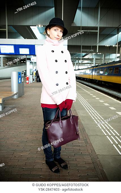Tilburg, Netherlands. Young adult fashionable woman commuting by train towards an assignment as music teacher