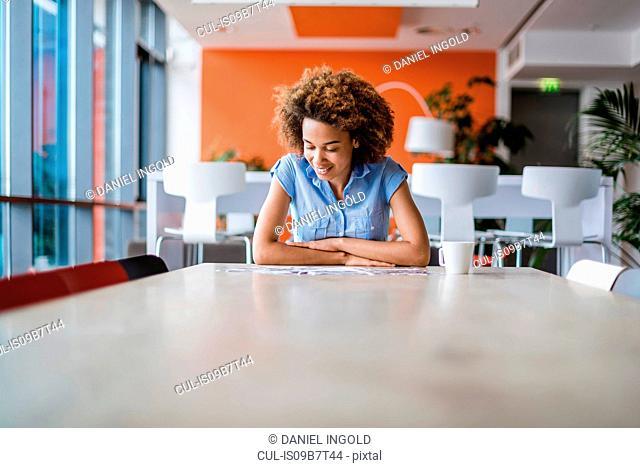 Young woman at table looking at brochures