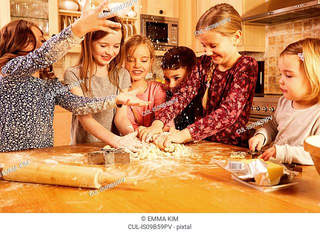Boy and girls fooling around while baking at kitchen table