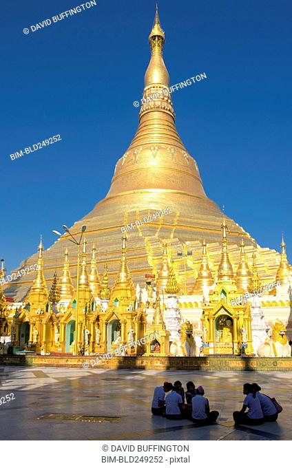 People sitting on ground outside golden pagoda