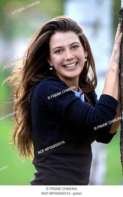 portrait of a beautiful brunette standing in birch forest