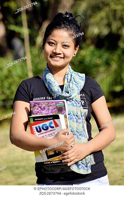 Beautiful young girl-student holding textbooks outside in the garden, Pune, Maharashtra