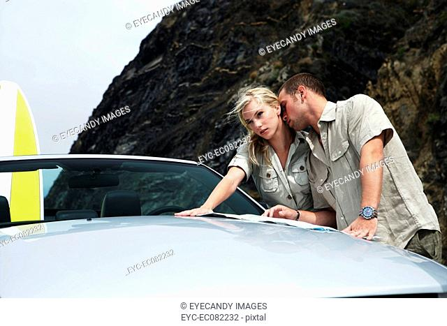 Young affectionate couple leaning on convertible with roadmap and surfboard
