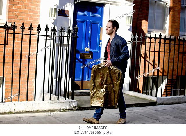 A young man carrying his drycleaning