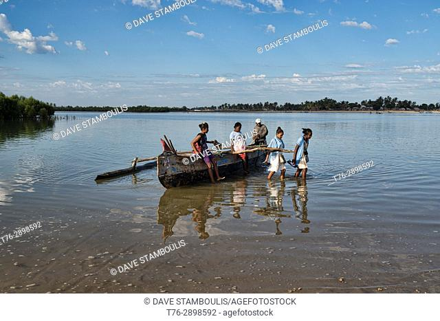 Schoolgirls travelling by pirogue on an inlet off the Indian Ocean, Morondava, Madagascar