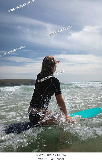 Woman sitting on surfboard looking at the sea