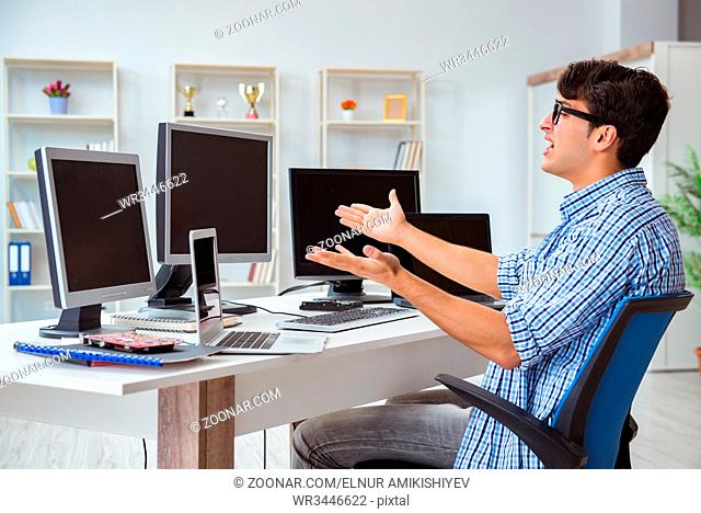 Businessman sitting in front of many screens