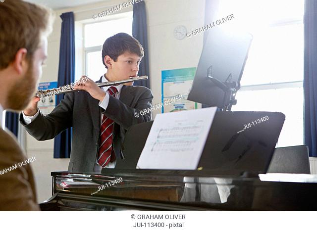 Middle school student playing flute with teacher playing piano in music class