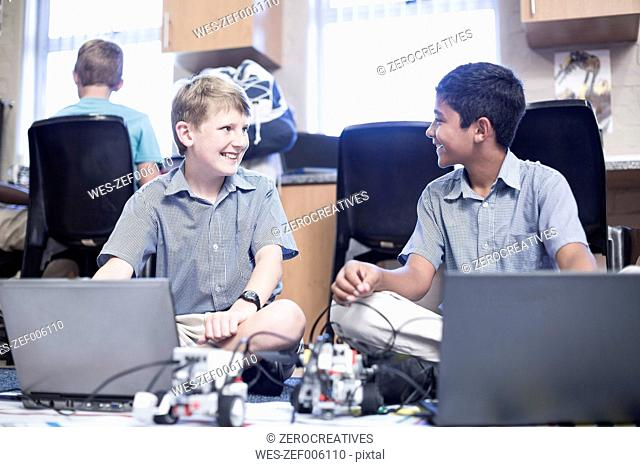Two smiling schoolboys with laptops in robotics class