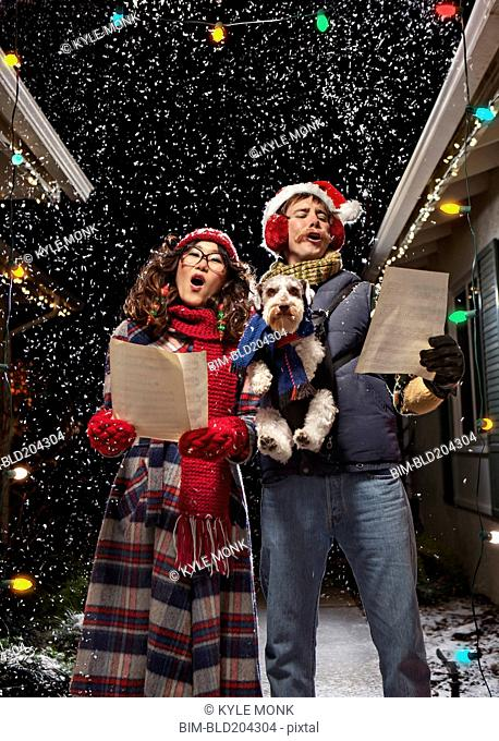 Couple singing Christmas carols with dog