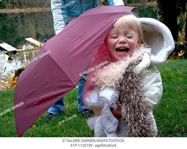 This two year old Caucasian toddler girl is crying outside under a burgundy colored umbrella She's wearing a white coat and white furry scarf and holding her...