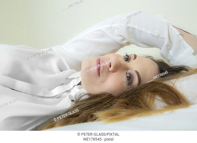 Young woman with long hair lying on her back on a bed