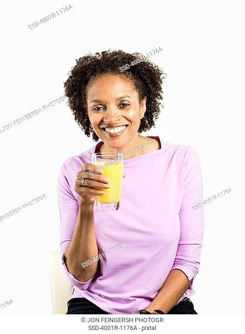 Portrait of a mid adult woman holding a glass of orange juice