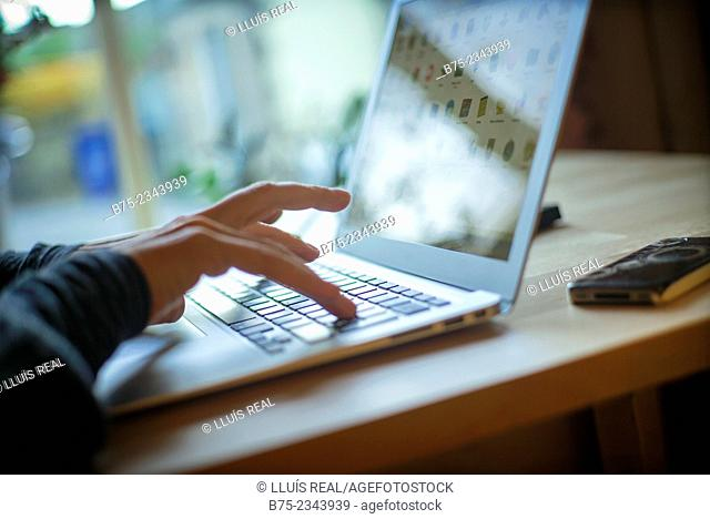 Closeup of female hands working with a laptop on a table in a cottage in Yorkshire Dales, England, UK
