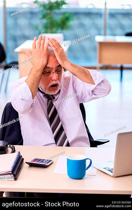 Old businessman employee unhappy with excessive work