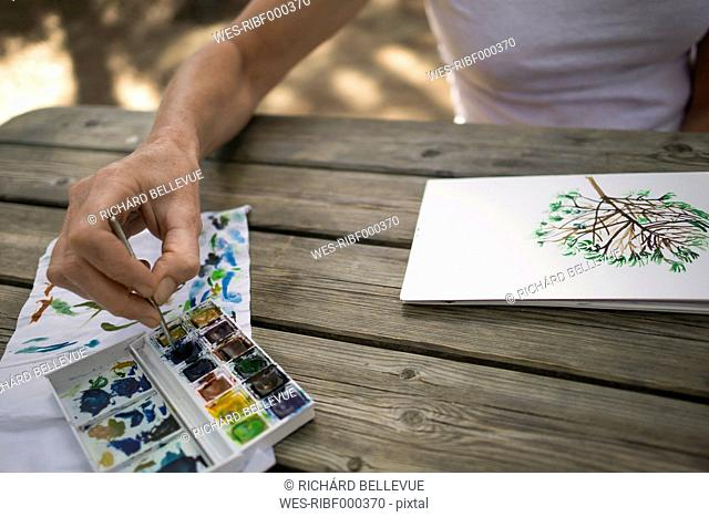 Woman painting tree on wooden table outdoors