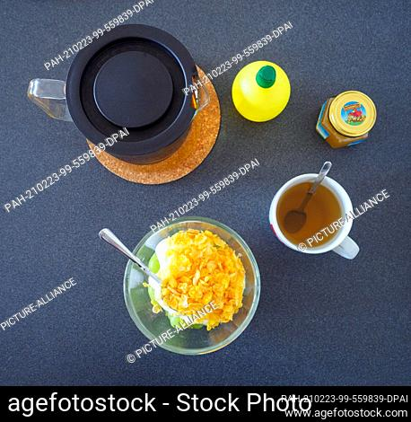 17 January 2021, Berlin: A glass pot of peppermint tea, a bowl with grapes, banana, yogurt and sugar-free cornflakes, a cup of tea