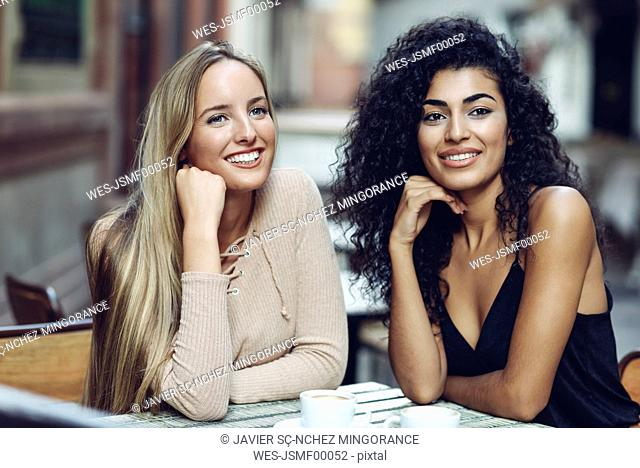 Portrait of two friends sitting in sidewalk cafe watching something