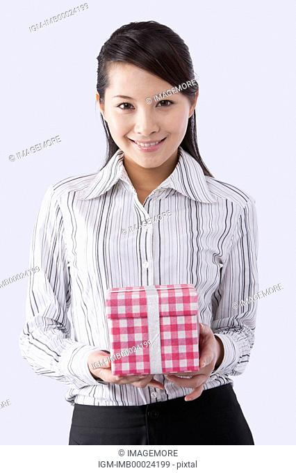 Young business woman holding a gift and smiling at the camera
