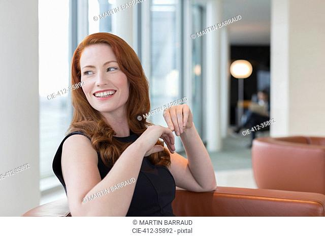 Smiling businesswoman with red hair looking over shoulder in lounge