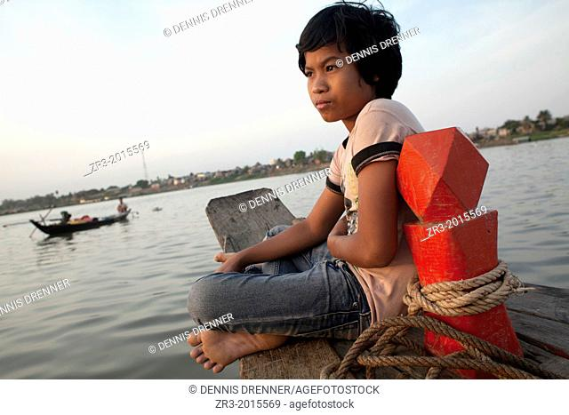 A young boy watches fisherman at work on the Mekong River early in the morning outside of Phnom Penh, Cambodia