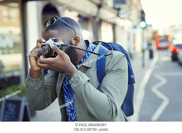 Young male tourist photographing with camera on street