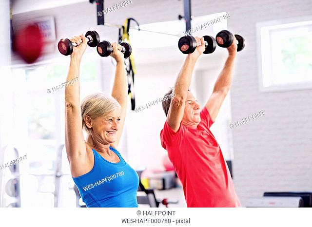 Mature woman and senior man working out in fitness gym