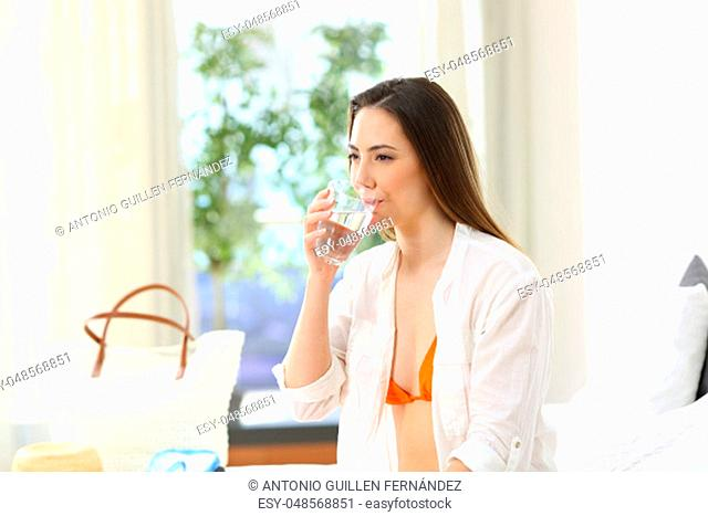 Woman drinking water from a glass in an hotel room on summer vacations on the beach