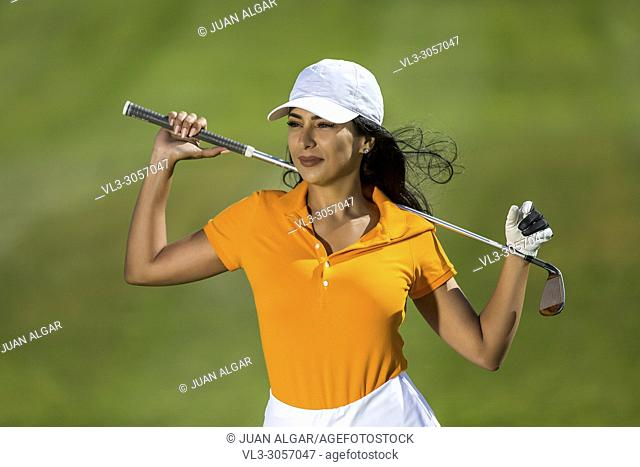 Pretty confident brunette wearing cap and golf trendy uniform posing confidently with driver on green background