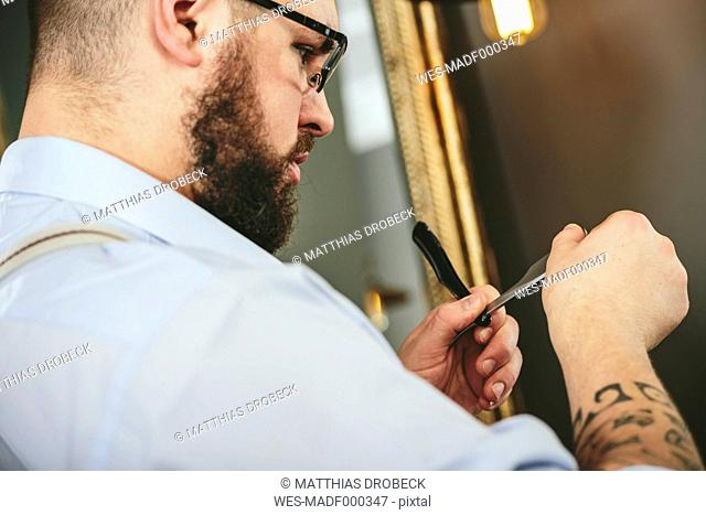 Barber checking blade of straight razor