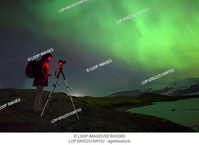 A photographer photographing the Aurora at Jokulsarlon Iceberg Lagoon