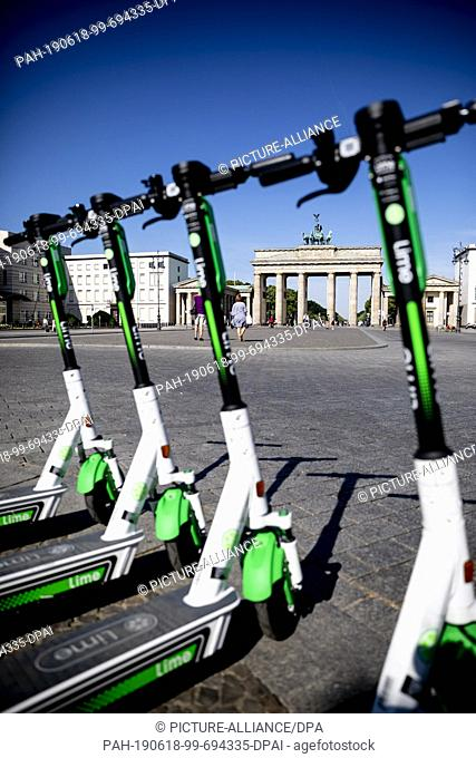 18 June 2019, Berlin: E- pedal scooters of the US-American company Lime are ready for rental in front of the Brandenburg Gate