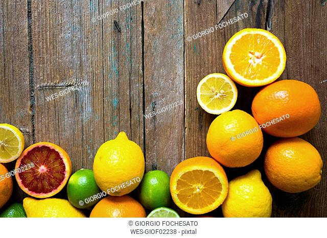 Sliced and whole lemons, oranges and limes on wood