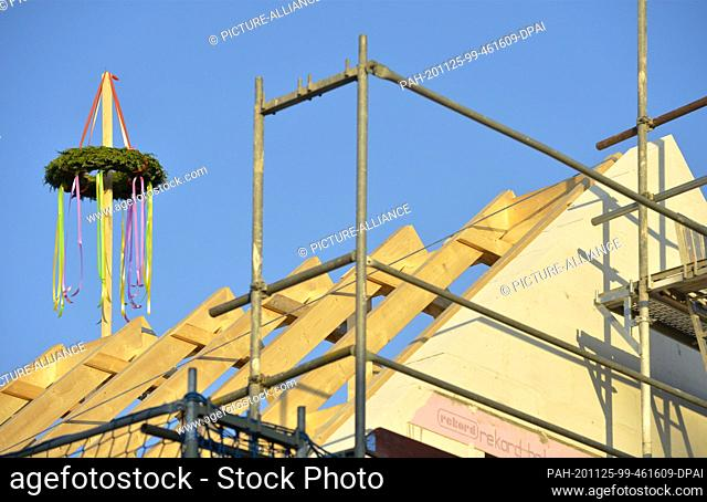 07 November 2020, Saxony, ---: A topping-out wreath is mounted on a new roof construction of a new detached house in a village in the Leipziger Land region