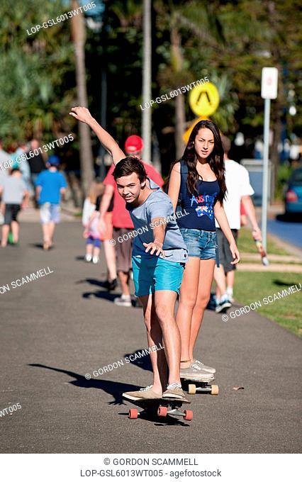 Australia, Queensland, Mooloolaba. Teenagers skateboarding along the seafront at Mooloolaba on the Sunshine Coast in Queensland