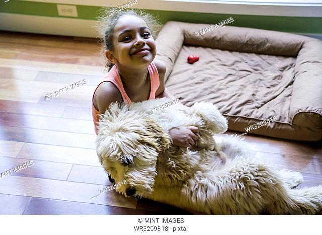Smiling girl sitting on floor hugging labradoodle puppy
