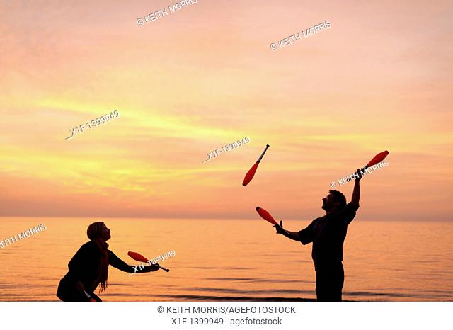 A young couple Juggling with clubs on the beach, spring evening sunset, Aberystwyth Wales UK