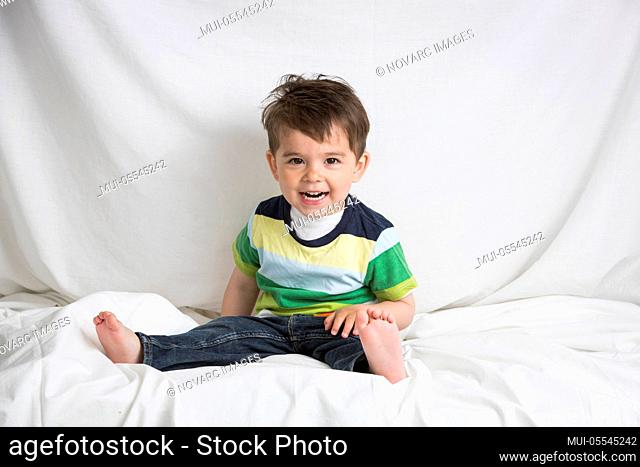 Little boy is sitting on a bed