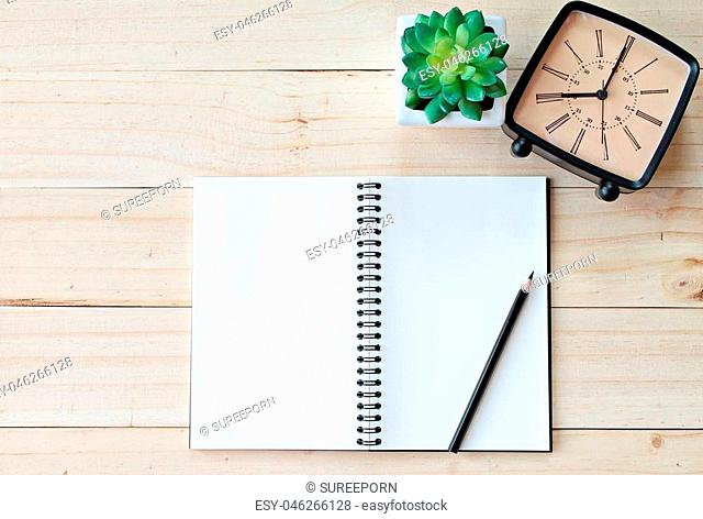 Still life, business, office supplies or vintage concept : Top view of working desk with blank notebook with pencil, retro alarm clock and plant on wooden...