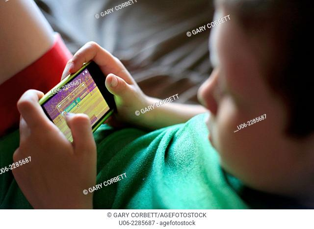 An 8 year old boy playing a game on an IPod or smartphone