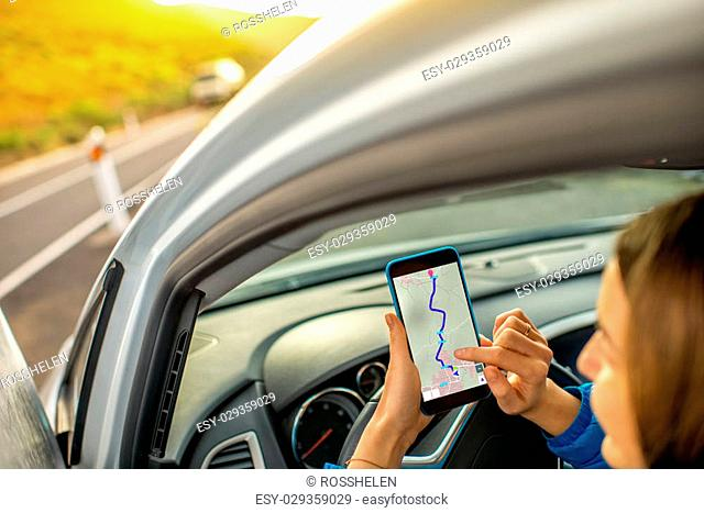 Young woman using smartphone with gps navigation sitting in the car