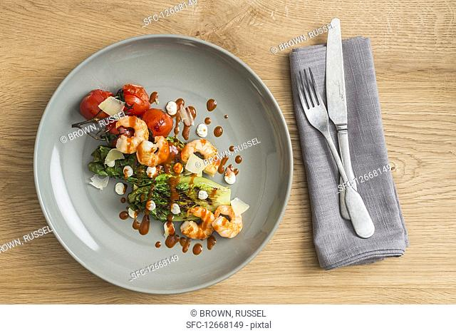 Roasted romaine lettuce hearts with shrimps and tomatoes