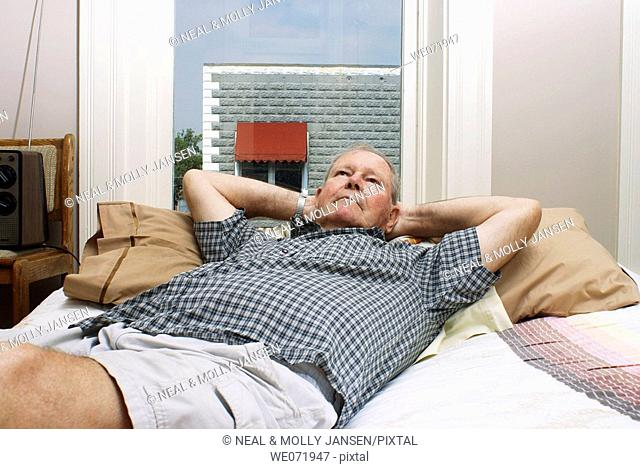 Elderly man rests comfortably on bed by window