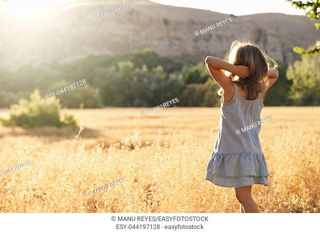 Young blonde girl playing with sunlight in the fields sunset wearing a dress with hill in the background