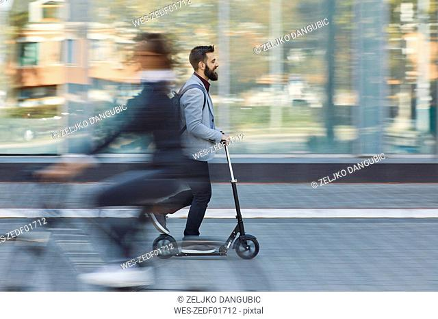 Businessman riding scooter along office building